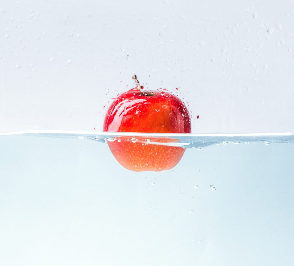 Apple with water splash on blue background