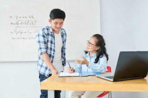 Math teacher explaining topic to schoolboy