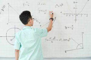 Schoolboy writing geometry equation