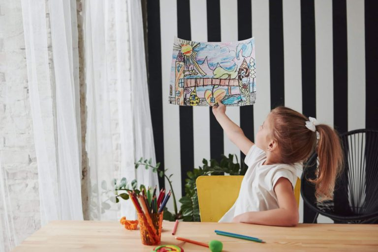 Cute little girl in art school shows her first paintings drawn by pencils and markers