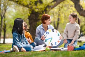 Teacher with small children sitting outdoors in city park, learning group education concept