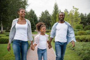 smiling african american family with little girl walking together in park