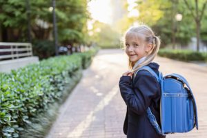 Schoolgirl back to school after vacations. Pupil in uniform and backpack early morning outdoor