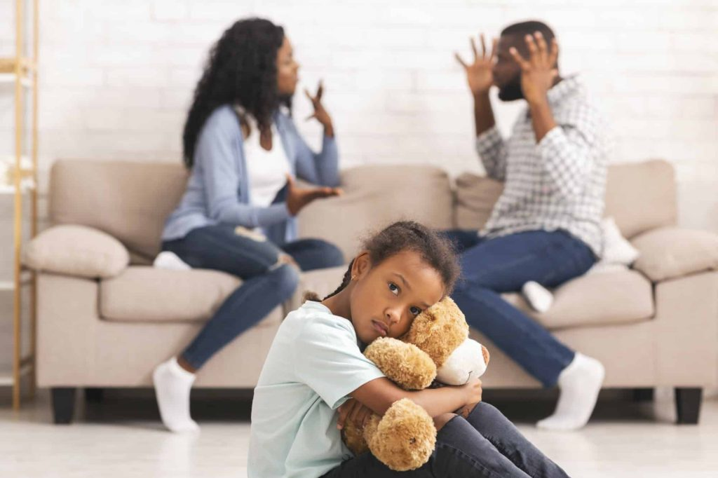 Child suffering from parents quarrels, sitting and cuddling teddy bear