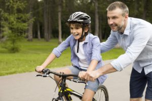 Boy learning to ride a bicycle with his father