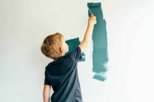 Caucasian blond boy paints a white wall with a roller in green. The child helps to make repairs.