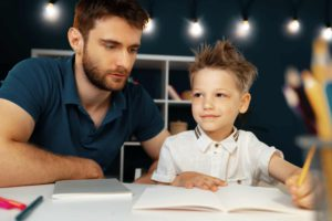 Dad and son doing school homework together