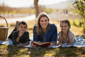 Smiling mother and kids reading novel in park