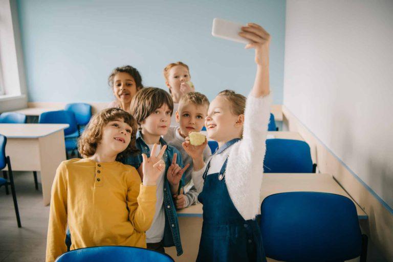 group of happy kids taking selfie at school classroom