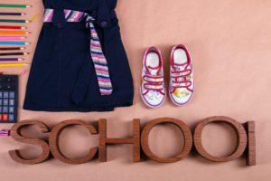 School uniform near sneakers and supplies on orange