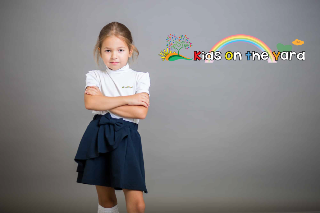 The girl, the schoolgirl, the second grader in a school skirt and white golfs poses on a gray