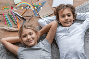 Happy children. Top view of childrens lying at home on floor with school things there
