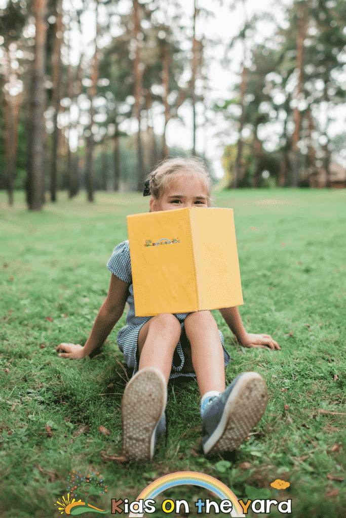 Back to school. Elementary school kid sitting on green grass with book at open-air class